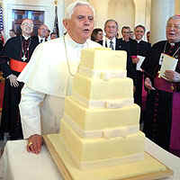 Pope Benedict XVI blow out birthday candle on top of his White House cake for his 81st birthday on April 16